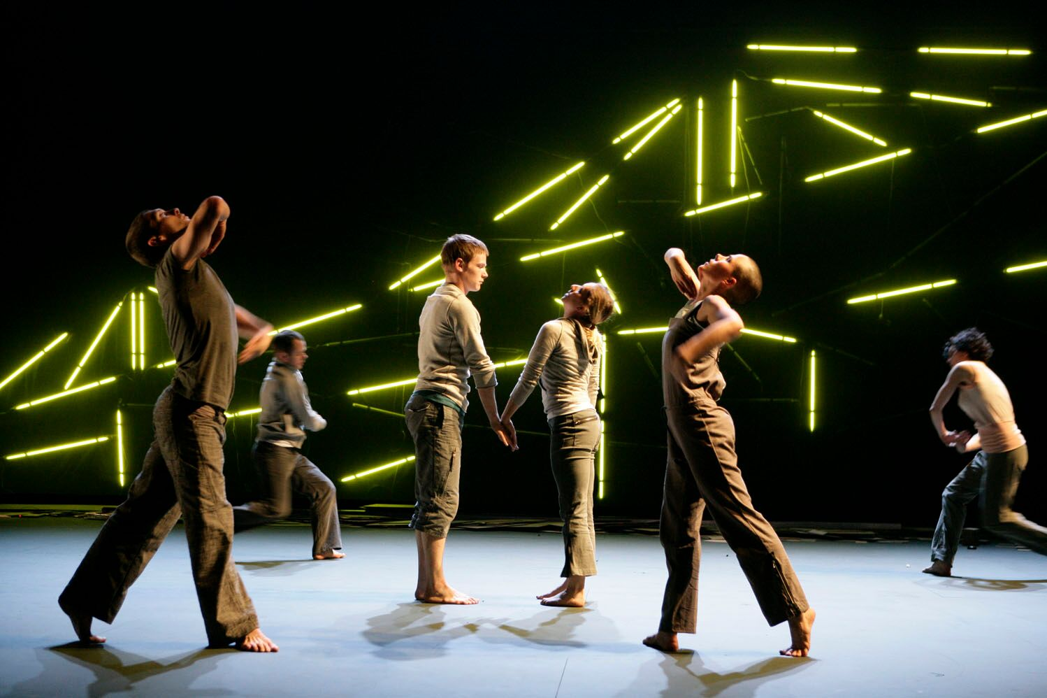 Six dancers dressed in khaki and plain-grey clothes fill the image. The stage is matt-grey with a black background. It features an array of lime coloured fluorescent lights arranged in a way that suggests a bridge.