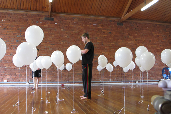 Several white, helium balloons are dispersed throughout the Lucy Guerin recital room. Each balloon is anchored to the floor with white string and are floating at waist height. A man stands in the middle of the room inspecting