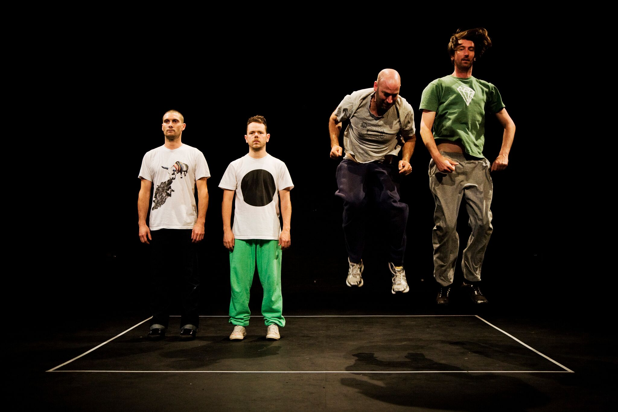 Four men dressed in casual street cloths stand in a black room. A thin white tapped border surrounds them, two of the men are mid jump.