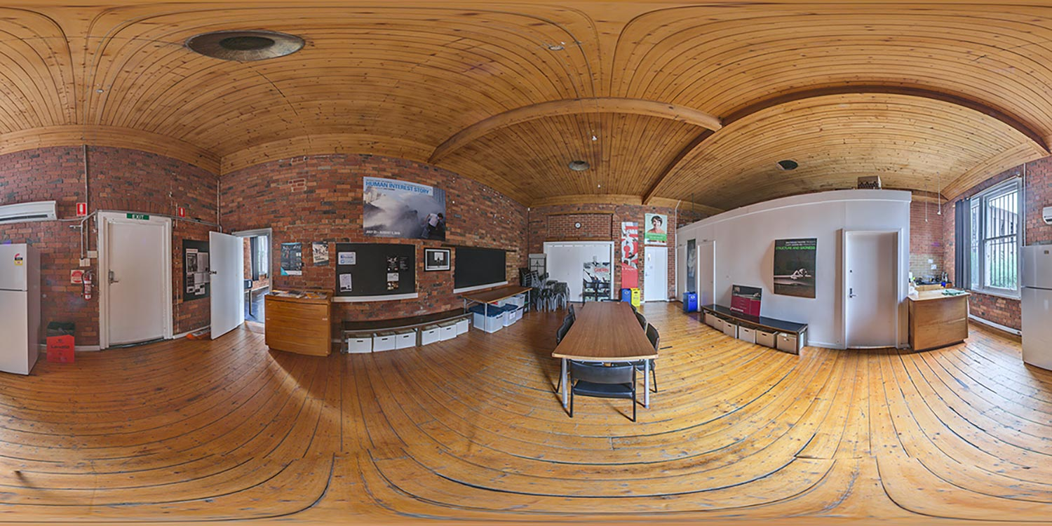 A 360-degree panorama of a room with red brick walls and a timber floor and ceiling.