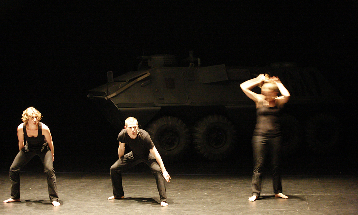 Three dancers dressed in black tight fitting work out clothes fill a stage. The two on the left are crouched and stare into the camera, the third is blurred with movement. In the background a tank fades into darkness.