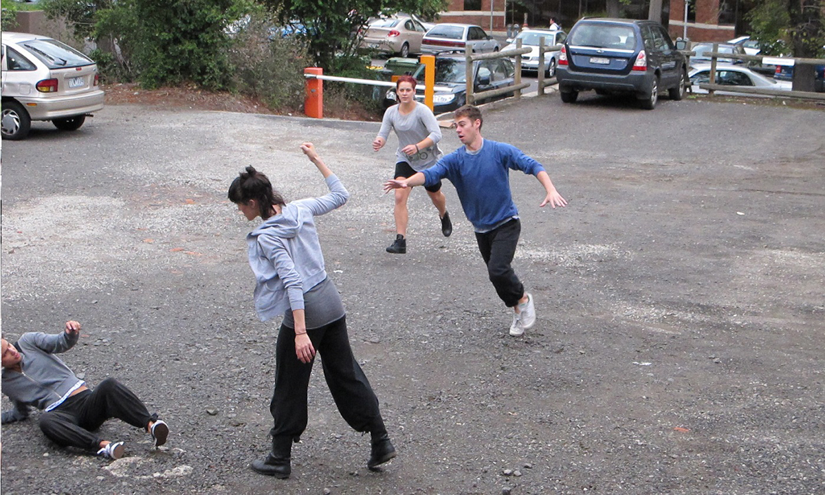 A woman in plain street clothes has her fist raised physically threatening a man whos cowering in fear. A man and a woman are rushing toward the violent scene. The scene is a drab suburban car park.